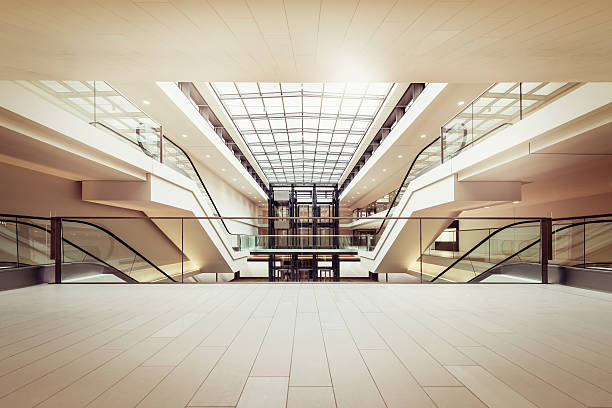 escalators in a clean modern shopping mall - shopping mall stock photos and pictures