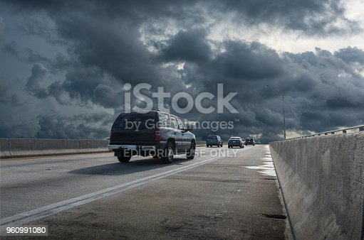 Miami, Florida, USA - May 13, 2018: Caravan of cars running at full speed fleeing from a storm at Key Biscayne causeway. Coastal regions are particularly vulnerable to the impact of a tropical cyclone or severe thunderstorm.