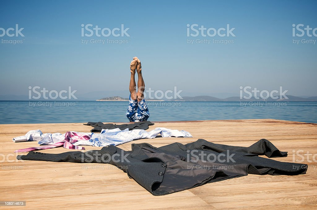 Escaping Businessman Leaves Suit Behind on Dock Diving into Sea royalty-free stock photo