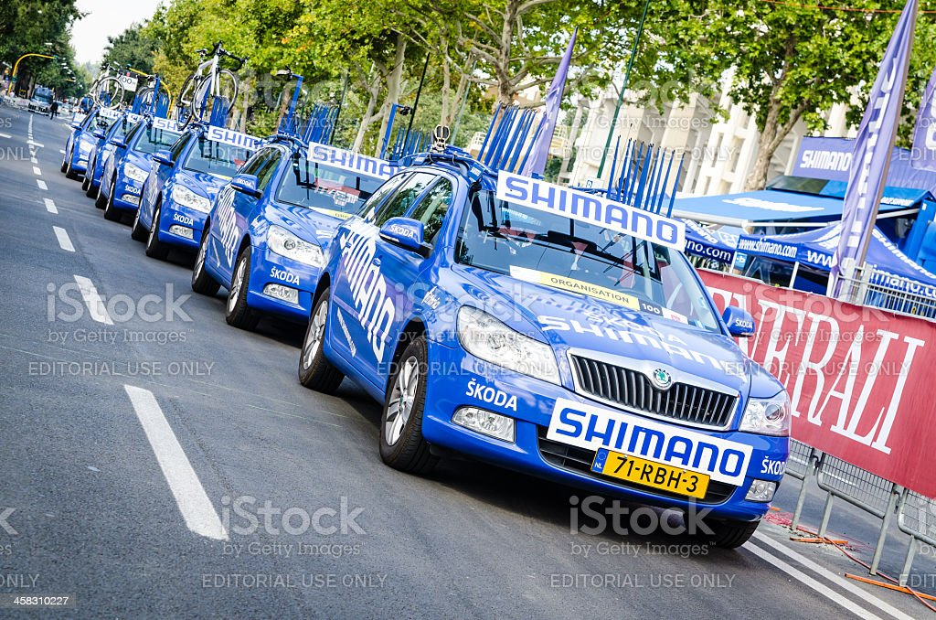Escort car in a row before cycling race stock photo