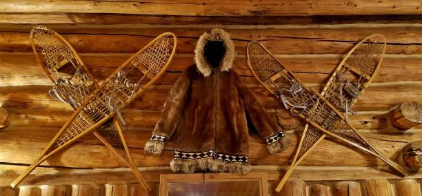 Eskimo Fur Jacket and 2 sets of Authentic Snow Shoes on a Wall stock photo