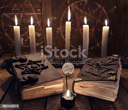 811119304 istock photo Esoteric still life with two black magic books and candles 682443574