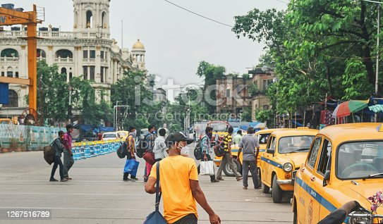 Esplanade, Kolkata, 7/12/2020: People are seen walking towards bus depot at Esplanade, which is one of the busiest bus terminus in city. Also retro looking ambassador taxis are waiting for passengers at roadside.