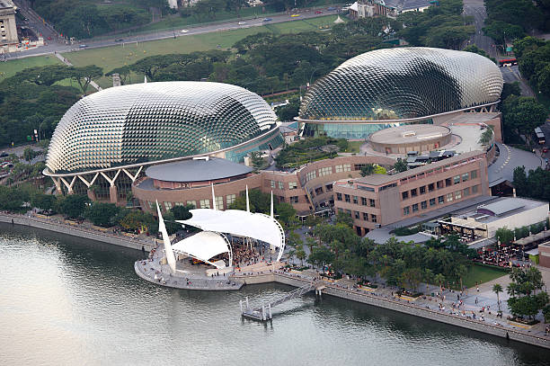 """Esplanade - Theatres on the Bay """"Singapore, Singapore - April 28, 2012: evening aerial view of famous building named Esplanade - Theatres on the Bay, a centre for arts performances located alongside Marina Bay. Under the large white tent like structure poeple gathering to listen to a music performance event."""" esplanade theater stock pictures, royalty-free photos & images"""