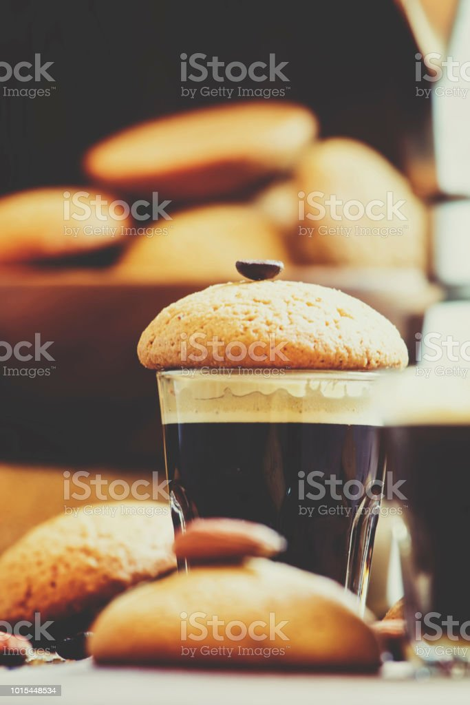 Espresso coffee, amaretti biscuits with almonds, neapolitan coffee maker, vintage wooden background, selective focus and toned image stock photo