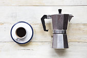 Espresso coffee and moka pot on grunge wooden table background.