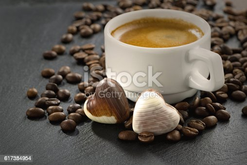 espresso, coffee beans and chocolate candies in a heart shape, close-up