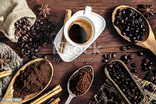 Espresso coffee cup on vintage table and assortment of grinded and roasted coffee beans