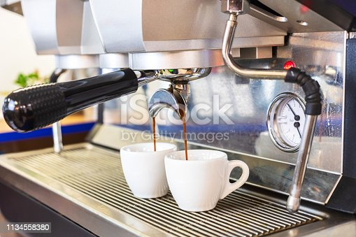 Espresso coffee machine brewing two shots in white cups, professional Italian equipment at restaurant or bar counter, close-up
