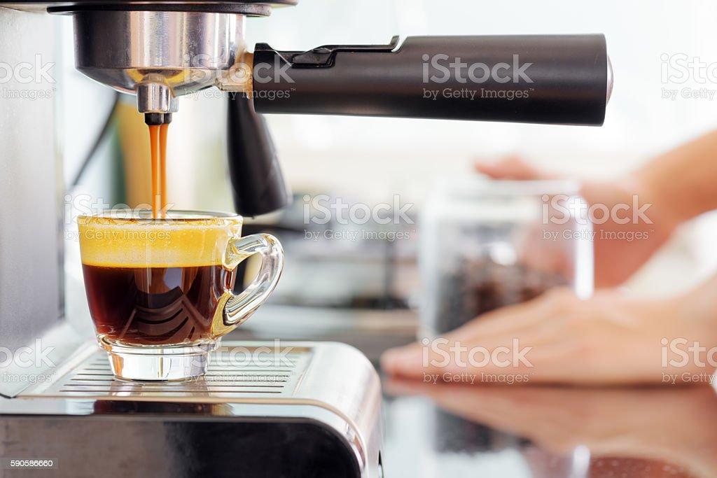 Espresso coffee machine in kitchen. Coffee pouring into cup stock photo