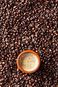 Espresso coffee mug over roasted coffee beans background