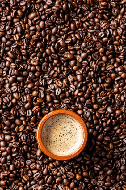 Espresso coffee mug over coffee beans stock photo