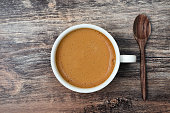 A cup of espresso coffee with wooden spoon, top view on wooden table background. Espresso coffee