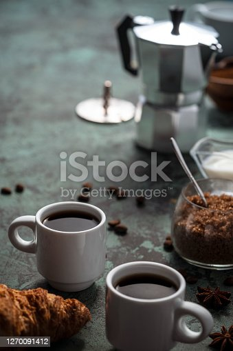 Espresso coffee two cups breakfast with croissant milk and sugar on green table and aluminium coffee maker