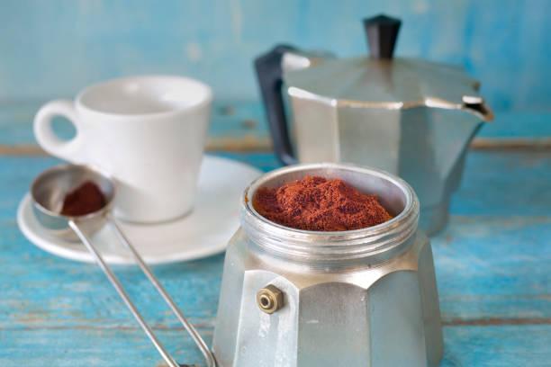 Espresso-Kaffee mit italienischer Espresso-Macher und Tasse, gemahlenem Kaffee, selektiver Schwerpunkt – Foto