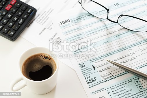 istock Espresso cup, income tax return form with calculator, glasses and pen on table 1094152532