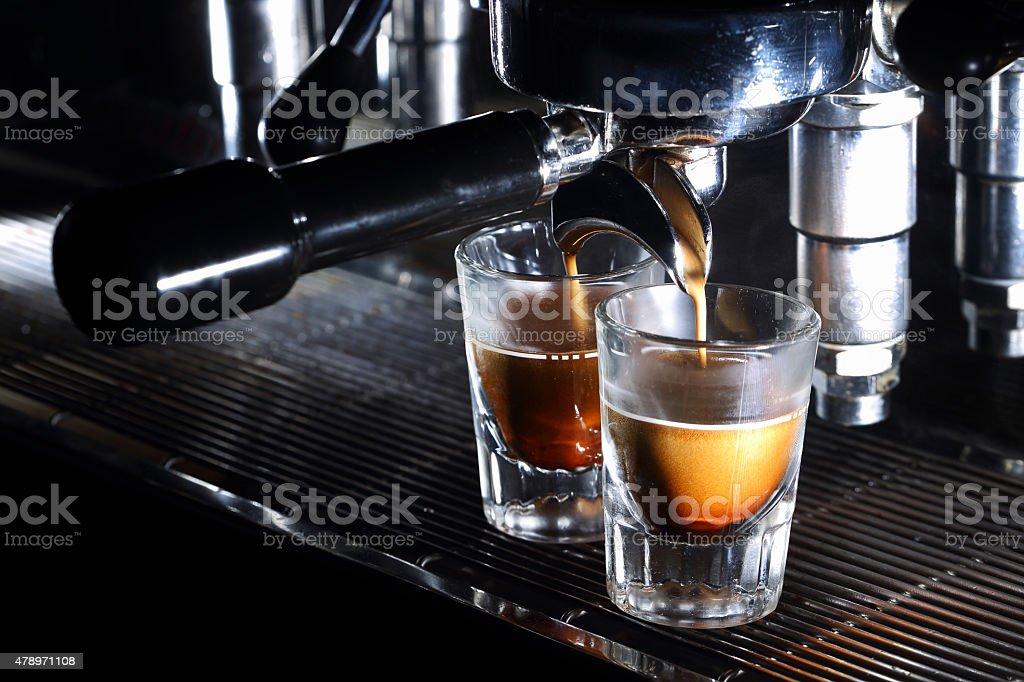 Espresso machine brewing a coffee. Coffee pouring into shot glasses stock photo