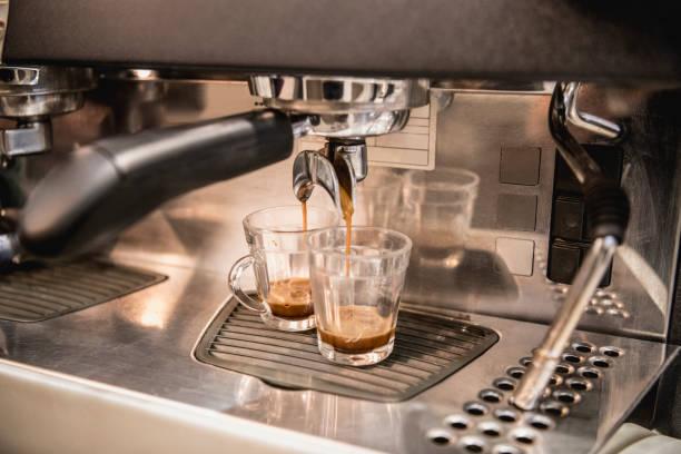 espresso machine filling two glass cups of coffee - argento metallo caffettiera foto e immagini stock