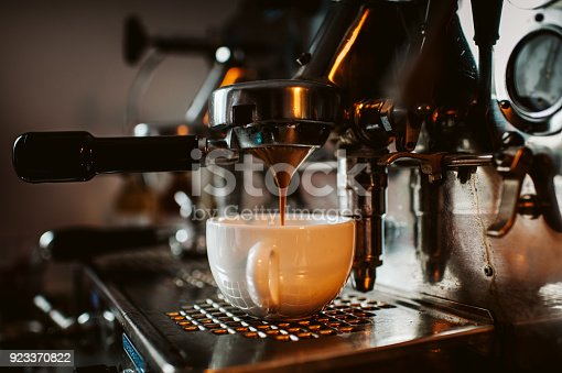 espresso machine pouring coffee into cups