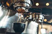 Fresh and hot espresso coffee pours from a portafilter on a nice chrome espresso machine.  Horizontal image.
