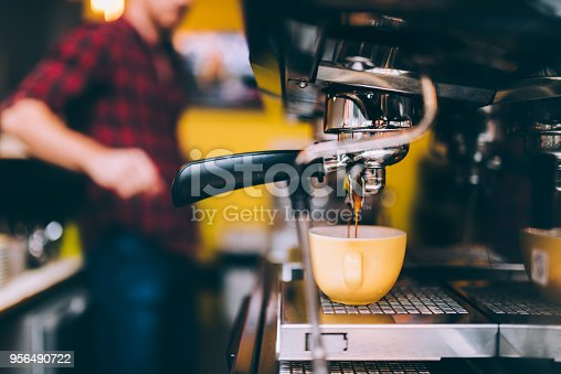 Espresso machinery pouring freshly brewed coffee in cafe shop. barista details and bartender