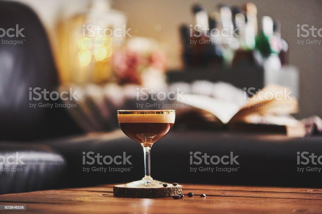 Espresso Martini cocktail in indoor-Einstellung mit Kaffeebohnen und Buch auf Couchtisch – Foto