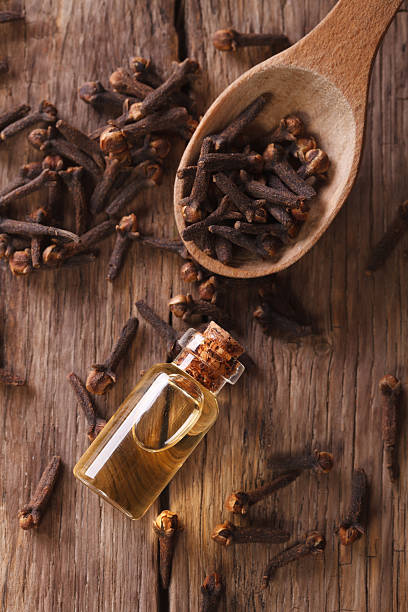 essence of cloves in the bottle macro  vertical top view The essence of cloves in the bottle close-up on the table. vertical view from above clove spice stock pictures, royalty-free photos & images