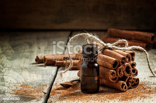 Essential cinnamon oil in a small bottle, ground cinnamon and cinnamon sticks on old wooden background, selective focus