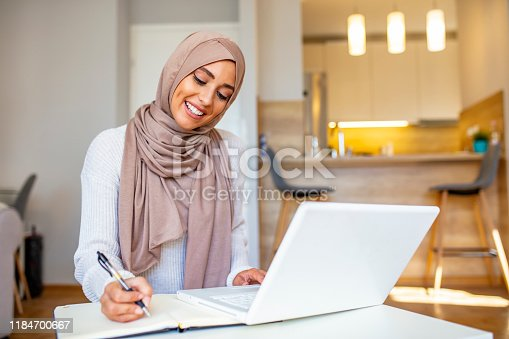 Attractive female Arabic working on laptop computer and paperwork's on desk. Arabian Businesswoman working at home. Dedication and technology. Essential for getting her tasks done