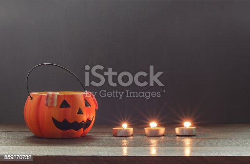 istock Essential items of Happy Halloween decorations festival concept background.Mix accessories candle and trick or treat bowl with candy & dessert on modern rustic brown wooden at home office studio desk. 859270732