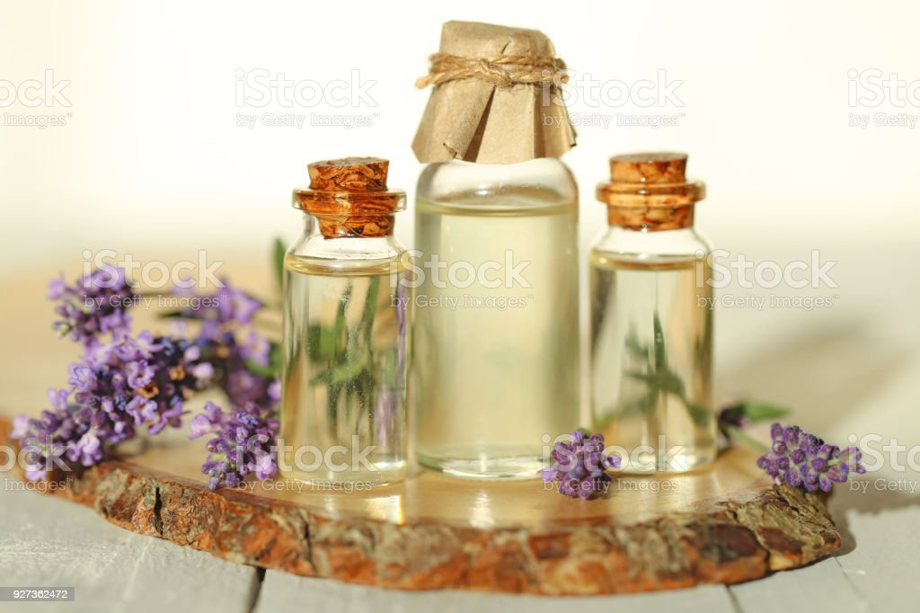 Essential lavender oil. Lavender oil set in glass transparent bottles and sprigs of fresh lavender on a wooden cut on a gray background. Botanical cosmetic - Royalty-free Aromatherapy Stock Photo