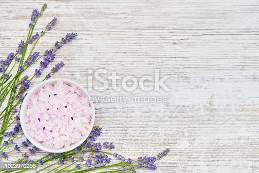 istock Essential lavender salt and lavender flowers on wooden background. SPA lavender products. Copy space 1023970256