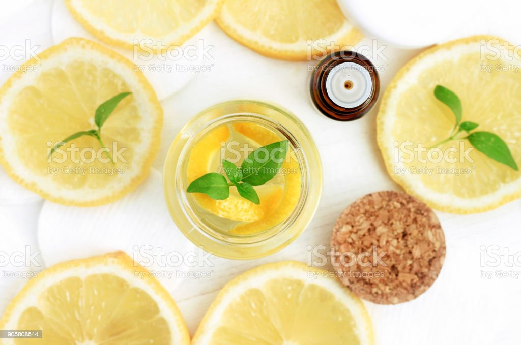 Essential lemon oil with fresh yellow citrus fruit slices viewed from above. stock photo