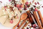 Herbal aroma beauty care. Dropper bottle, dried fragrant flowers, sticks, wooden utensils, top view background.