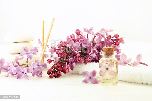 istock Essential oil bottle corked with flower inside in extract, fresh lilac, white light tones 689749512