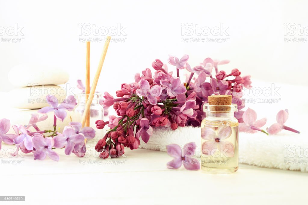 Essential oil bottle corked with flower inside in extract, fresh lilac, white light tones stock photo
