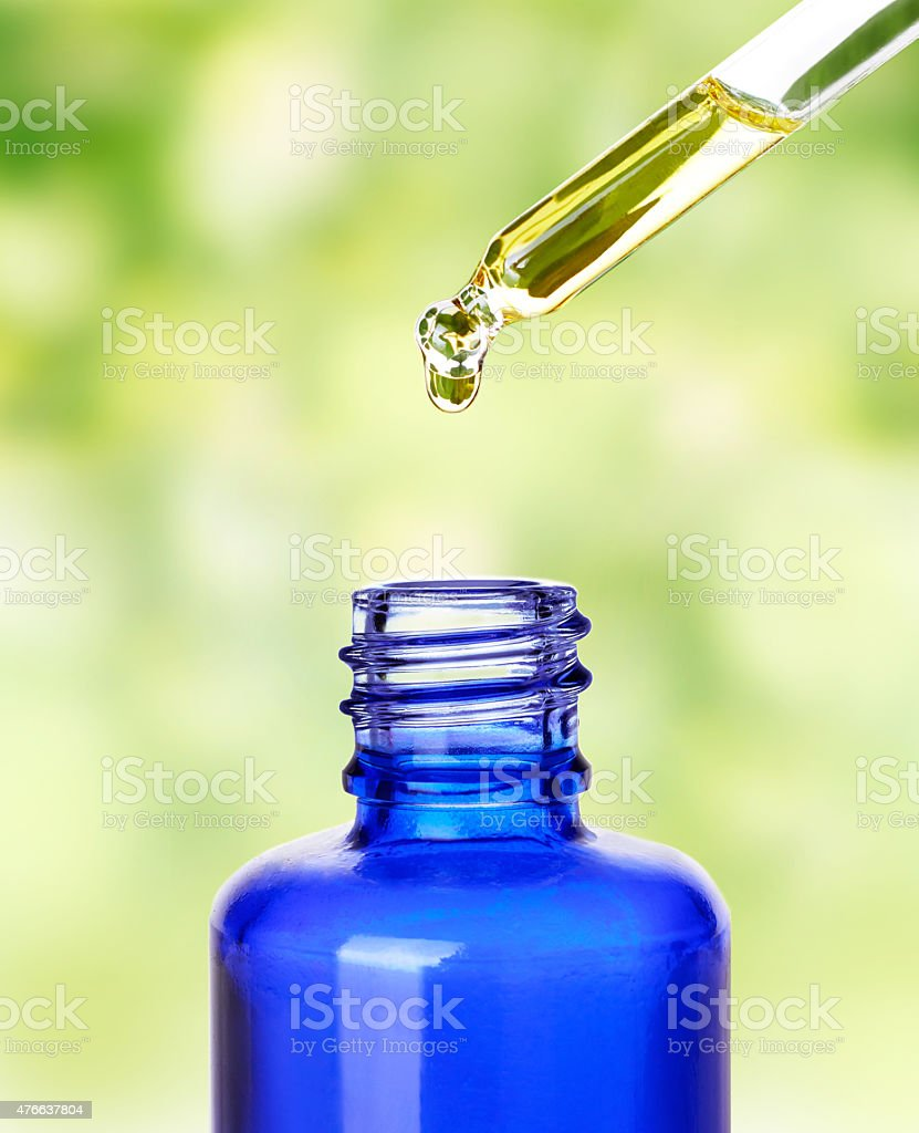 Essential oil dropping from pipette .Aromatherapy. stock photo