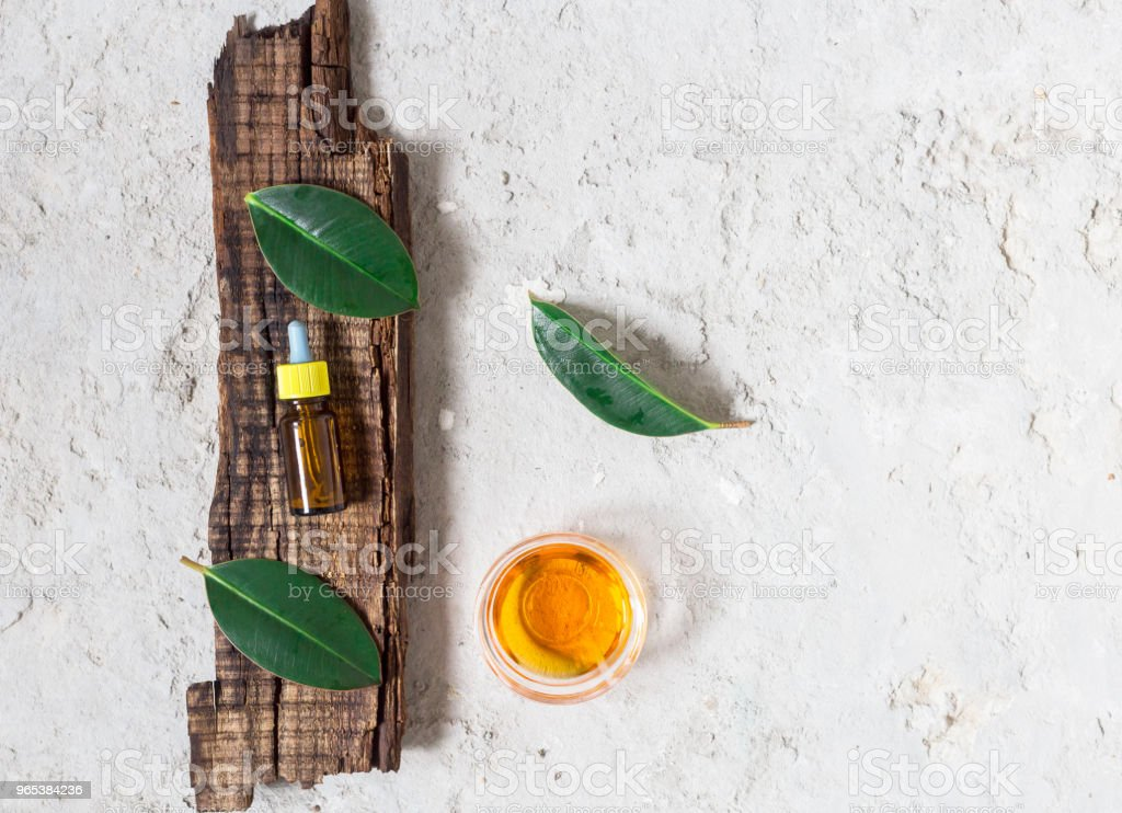 Essential oil in a bottle lies on an old wooden board. Cement background. Copy space royalty-free stock photo