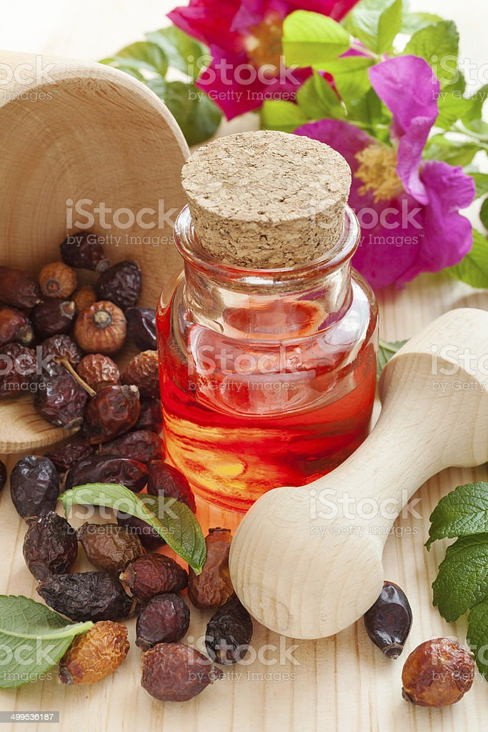 essential oil in glass bottle, dried rose-hip berries and flowers stock photo