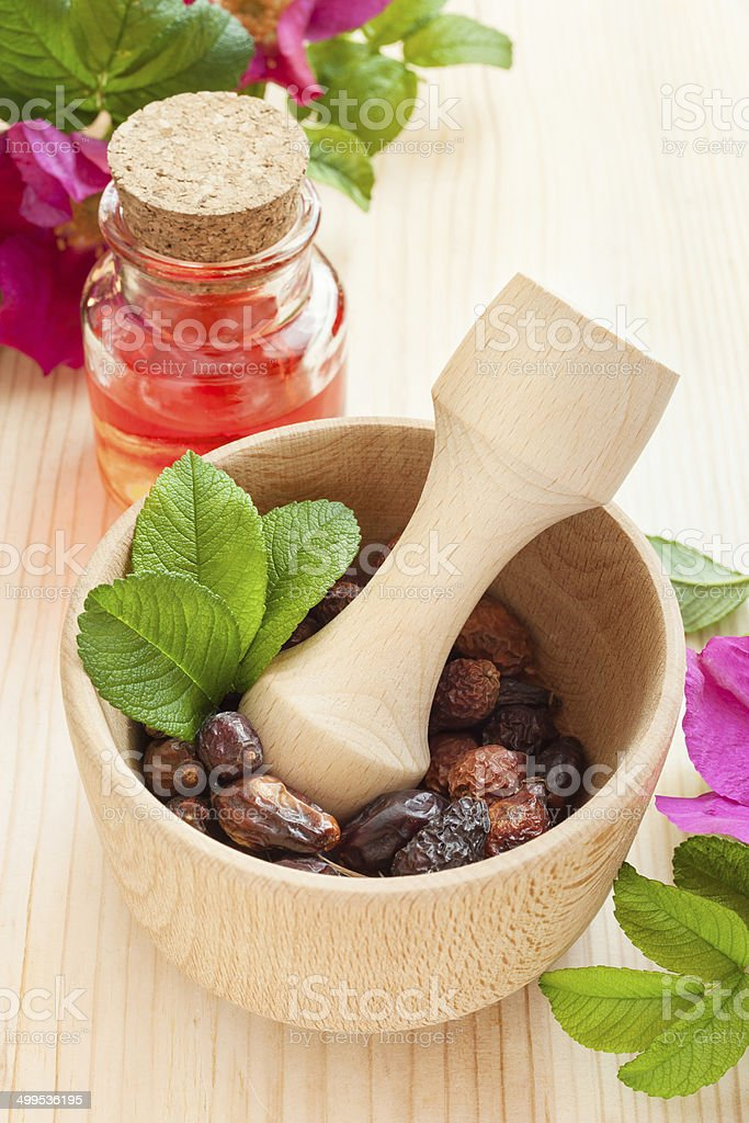 essential oil in glass bottle, flowers and dried  berries stock photo