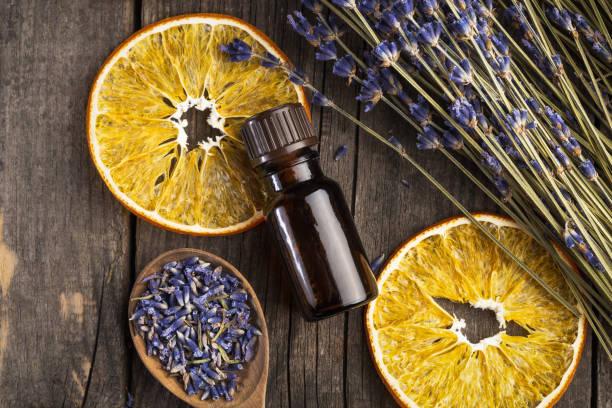 olejek eteryczny lawendy i pomarańczy suche na drewnianym stole, widok z góry - perfumowany zdjęcia i obrazy z banku zdjęć