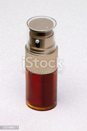 istock Essential oil liquid. Close-up of a brown glass spray bottle with a golden cap filled with beauty serum for face on a light pink glitter sparkle background. Anti aging woman. 1251698217