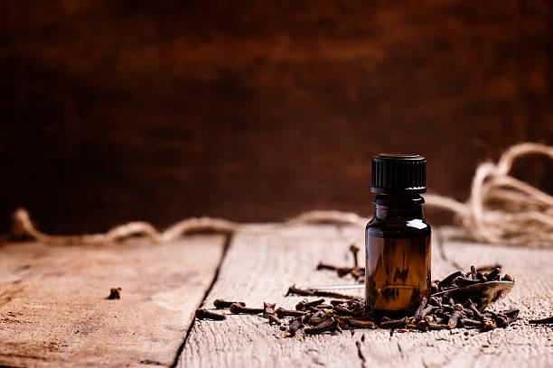 essential oil of cloves in a brown bottle - oli, aromi e spezie foto e immagini stock