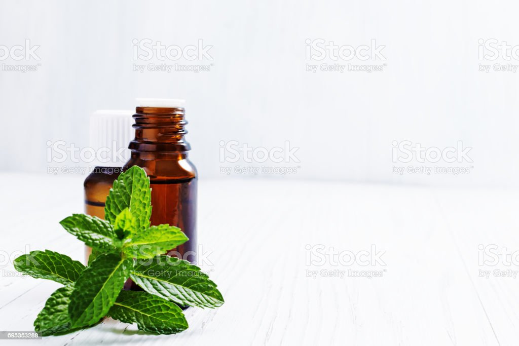 Essential oil of peppermint in dark bottles, fresh green mint on white wooden background, selective focus stock photo