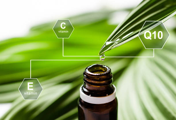 Essential oil or water dropping from fresh leaf to the bottle with digital vitamin icons. Q10, vitamin and other ingredients. stock photo