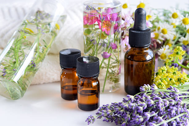 essential oils and natural cosmetics with herbs - aromaterapi stok fotoğraflar ve resimler