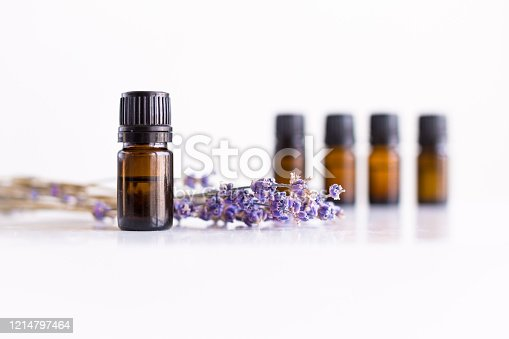 A row of essential oil bottles with lavender flowers and white background.