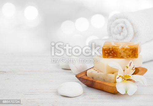 istock Essential spa products on wooden surface over abstract lights background 685470704