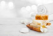 Essential spa products on wooden surface over abstract lights background