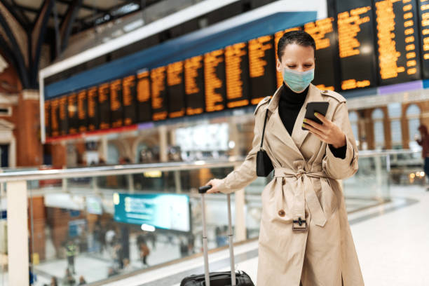 Essential travels during lockdown - woman with face mask checking in online while waiting near arrival departure board stock photo